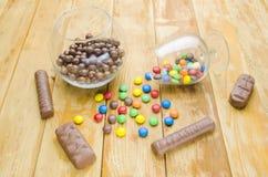 doces Multi-coloridos em um fundo de madeira imagens de stock