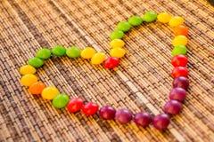 Doces que formam uma forma do coração bombom colorido no guardanapo da palha como um coração Textura de bambu da esteira do guard imagem de stock