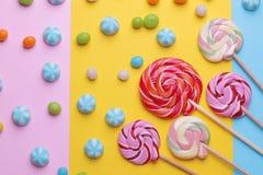 Doces redondos coloridos e pirulitos coloridos em fundos brilhantes coloridos Foto de Stock