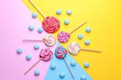 Doces redondos coloridos e pirulitos coloridos em fundos brilhantes coloridos Fotos de Stock