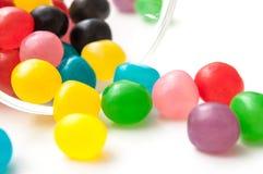 doces redondos coloridos que caem do recipiente de vidro o Fotografia de Stock