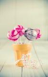 Doces redondos do pirulito em um copo alaranjado Imagem de Stock