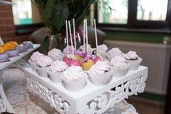 Doces redondos doces do rosa e do amarelo em uma vara e em queques para a barra de chocolate Tabela com os doces saborosos prepar Foto de Stock Royalty Free