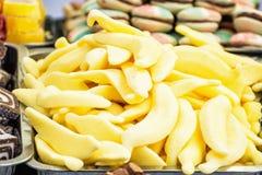 Doces saborosos amarelos do alcaçuz no recipiente plástico Imagem de Stock