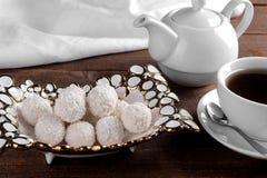 Doces doces saborosos do coco em um vaso com chá em uma tabela de madeira marrom imagem de stock