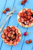 Doces saudáveis Morangos suculentas frescas em tartlets com creme Foto de Stock