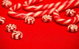 Doces vermelhos e brancos do caramelo na serapilheira vermelha Foto de Stock Royalty Free