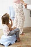 Dochter Aarzelend om Tanden met Moeder te borstelen royalty-vrije stock afbeeldingen