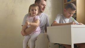 Dochter die aan vader en zoon komen die thuiswerk doen bij bureau stock footage