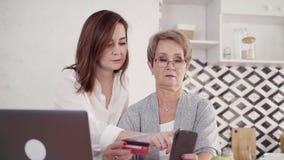 Dochter die haar hogere moeder helpen die online het winkelen met s maken stock videobeelden