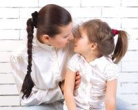 Dochter die haar moeder kussen stock foto
