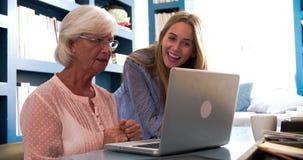 Dochter die Hogere Moeder met Computer in Huisbureau helpen stock video
