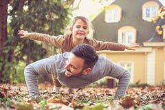 Dochter die op Vaders terug vliegen stock afbeeldingen