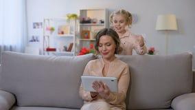 Dochter die tulpen jonge moeder met tablet, de traditie van de vakantieverrassing voorstellen stock footage