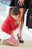 Dochter die zich aan het Been van de Moeder vastklampen stock foto