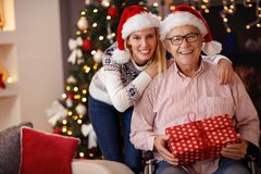 Dochter en bejaarde vader in rolstoel het vieren Kerstmis stock foto