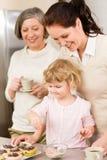 Dochter en de moeder die cupcakes bestrooien de verfraaien Stock Foto