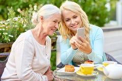 Dochter en hogere moeder met smartphone bij koffie royalty-vrije stock foto