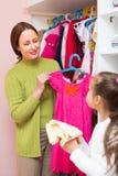 Dochter en mamma die kleding kiezen Stock Afbeeldingen