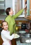 Dochter en moederwasschotels Stock Foto's
