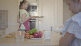 Dochter gietende melk in een glas, en gelukkig mamma die vers gebakken broodjes van de oven in comfortabele keuken terugtrekken stock footage