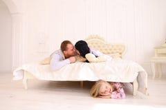 Dochter het verbergen onder thuis gesproken bed, Mamma en Papa stock foto's