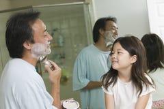 Dochter Lettende op Vader Apply Shaving Cream in Badkamers royalty-vrije stock foto