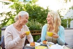 Dochter met hogere moeder het drinken thee bij koffie stock foto's