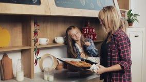 Dochter met mamma in de keuken Het mamma geeft vers gebakken koekjes aan haar dochter De koekjes van het familieontbijt met melk stock video