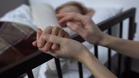 Dochter ondersteunend haar terminaal zieke moeder die op het ziekenhuisbed liggen, armenhuis stock videobeelden