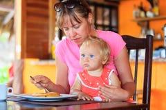 Dochter van de moeder de voedende zuigeling in koffie royalty-vrije stock foto's