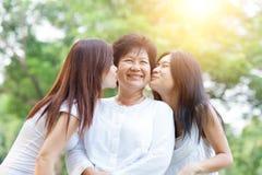 Dochters die bejaarde moeder kussen royalty-vrije stock foto's