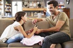 Dochterzitting op de Spijkers van Sofa At Home Painting Father ` s royalty-vrije stock foto's