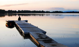 On the Dock. Image taken of someone relaxing alone at the end of a dock Stock Image