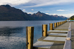 Dock. Empty dock in calm lake with mountains in the horizon stock image