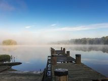 Dock against misty river. In the early morning Royalty Free Stock Photography