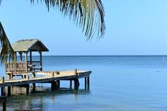 Dock along the Caribbean Ocean, Roatan, Honduras. Covered Dock in Roatan, Honduras framed by a palm tree Stock Photo