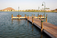 Dock in the Arizona desert. Palm tree lined lakeshore with fishing dock and ducks by mountains in the desert near Phoenix, Arizona Stock Photos