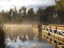 Dock auf nebelhaftem nebeligem See Lizenzfreies Stockbild