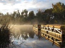 Dock auf nebeligem See des Sonnenaufgangs Stockfotos