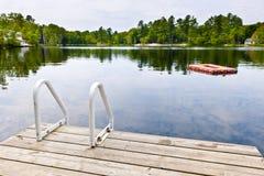 Dock auf ruhigem See im Häuschenland Stockfotos
