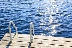 Dock auf Sommersee mit funkelndem Wasser Stockfotografie