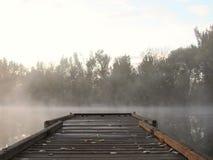 Dock auf Sonnenaufgangsee Stockfotos
