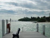 Dock avec de l'eau de négligence banc un jour nuageux photographie stock
