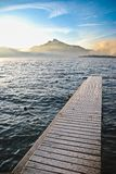Dock on beautiful lake behind mountain Stock Photo