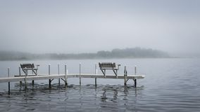 Dock with benches on foggy lake in Bemidji Minnesota. Dock with benches on foggy Lake Irving in Bemidji Minnesota stock photos
