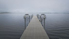 Dock with benches on foggy lake in Bemidji Minnesota. Dock with benches on foggy Lake Irving in Bemidji Minnesota royalty free stock images