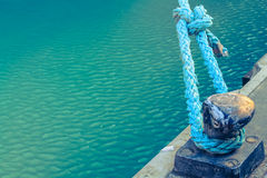 Dock with blue rope in harbor with turquoise water. Stock Photos