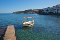 Dock and boat in Cadaques Bay. A single boat docked in Cadaques Bay surrounded by the green-blue sun dappled water of the Mediterranean Sea Stock Image