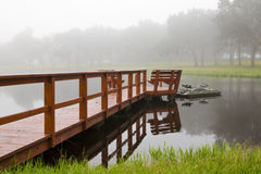 Dock and boat on foggy morning. Wooden plank dock or pier leading to small fishing boat on lake river pond on a foggy day morning royalty free stock photo